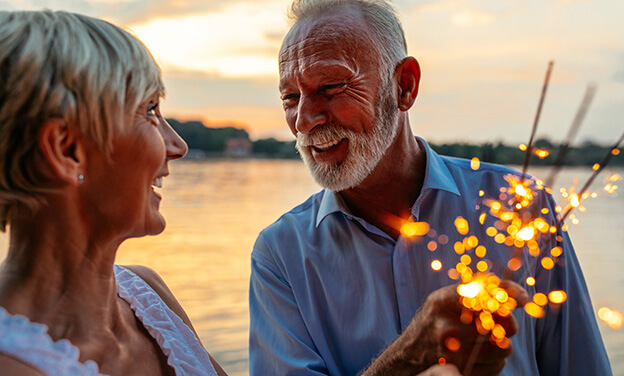senior couple holding sparklers on the 4th of July