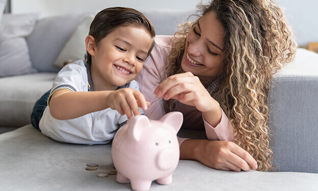 mother and young son putting money in a piggy bank